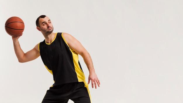 コピースペースでバスケットボールを投げる準備をして男性プレーヤーの正面図