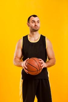 バスケットボールを保持しながらポーズをとって男性プレーヤーの正面図