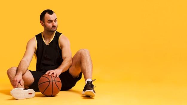 ボールとコピースペースで座っている男性のバスケットボール選手の正面図