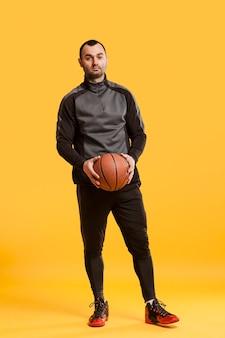 Вид спереди мужской игрок позирует расслабленной с баскетболом