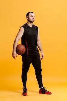 バスケットボールでポーズをとってリラックスした男性プレーヤーの正面図