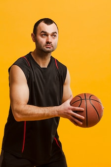 Вид спереди мужской игрок позирует с баскетболом