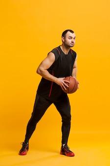 Вид сбоку мужской игрок позирует с баскетболом