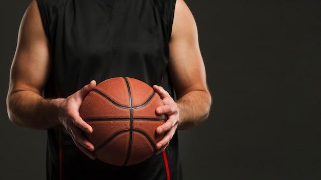コピースペースを持つ男性プレーヤーによって開催されたバスケットボールの正面図