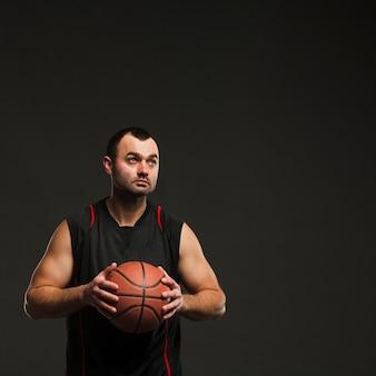 Вид спереди игрок мужского пола, держа баскетбол с копией пространства