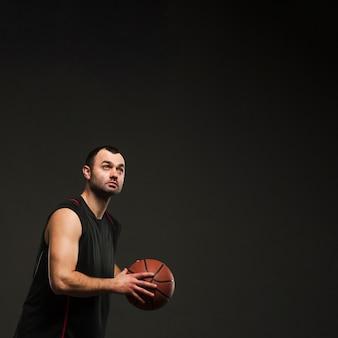 Взгляд со стороны игрока мужского пола держа баскетбол с космосом экземпляра