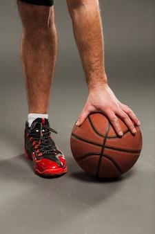 男性プレーヤーによって押されたバスケットボールの正面図