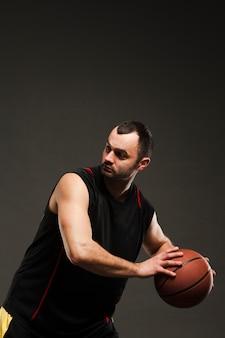 ボールとコピースペースを持つバスケットボール選手の側面図