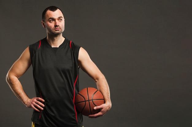 ボールとコピースペースでポーズのバスケットボール選手の正面図
