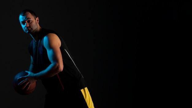コピースペースでポーズのバスケットボール選手の側面図
