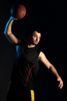ダンクシュートの準備のバスケットボール選手の正面図