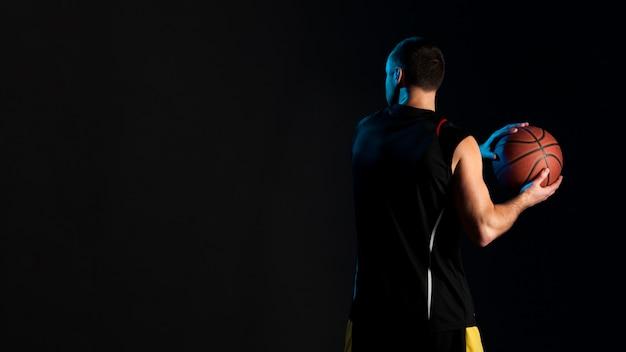ボールとコピースペースを持つバスケットボール選手の背面図
