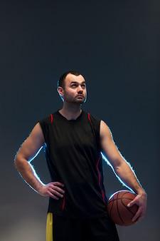 ボールとコピースペースを持つバスケットボール選手の正面図