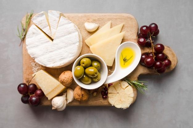 Вид сверху ассортимент различных деликатесов на деревянной доске