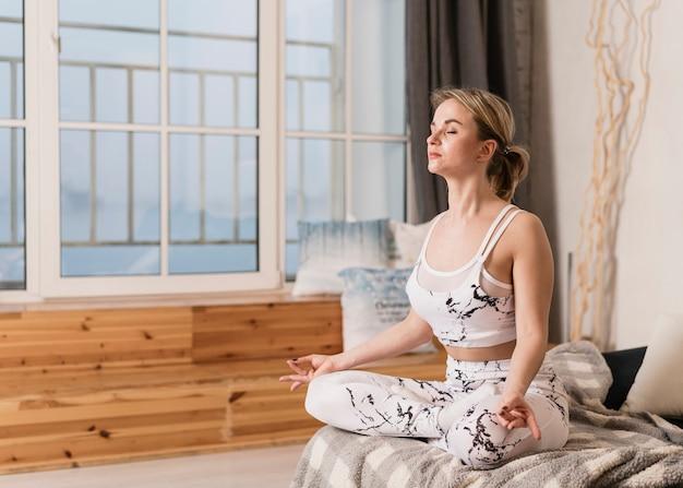 Женщина высокого угла делая йогу