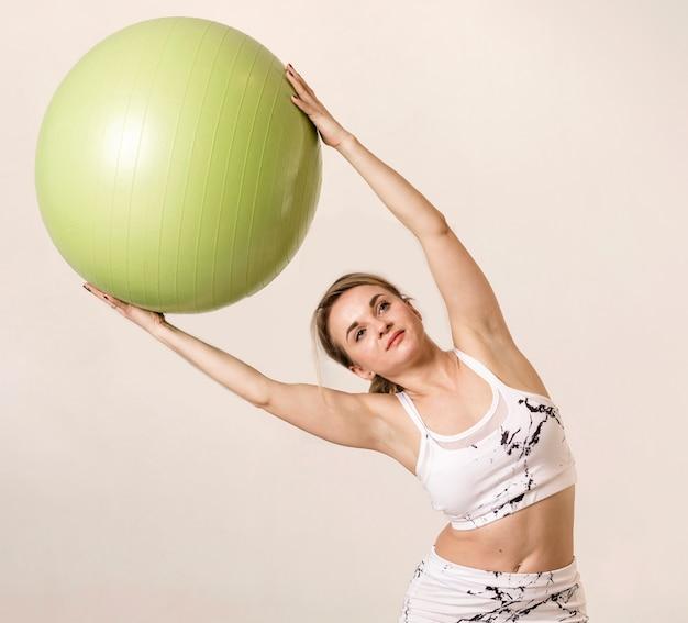 Женщина делает упражнения с фитнес-мячом