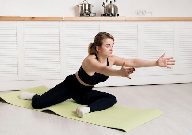 Женщина дома тренируется на коврике
