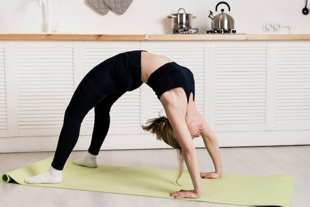 マットの上の自宅で若い女性トレーニング