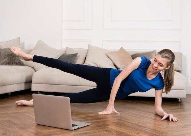 Девушка тренируется дома во время просмотра инструкций
