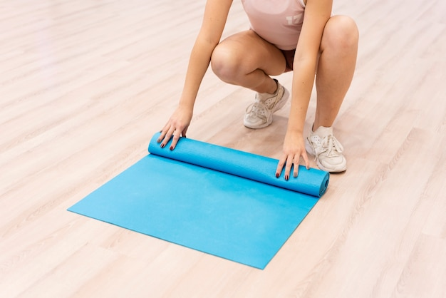Крупным планом женщина прокатки фитнес мат после тренировки
