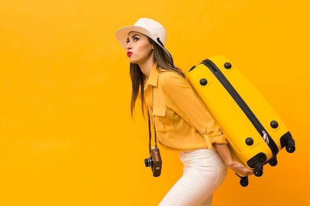 荷物とコピースペースを持つカメラを運ぶ女性の側面図