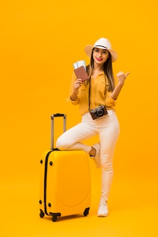 Вид спереди женщины, готовой к отпуску с багажом и предметами первой необходимости путешествия