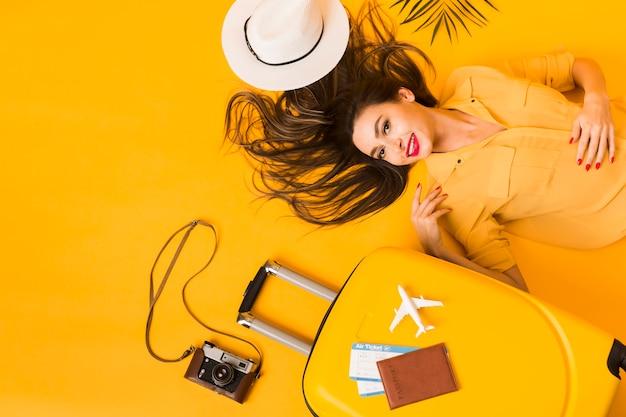 旅行の必需品を持つ女性のフラットレイアウト