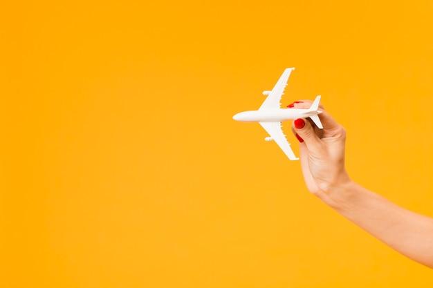 コピースペースを持つ飛行機の置物を持っている手の正面図
