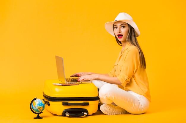 荷物の上にラップトップに取り組んでいる間帽子をかぶっている女性の側面図