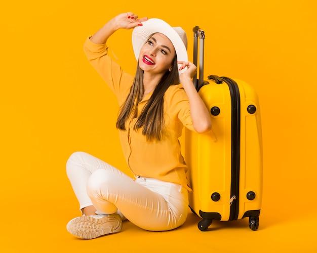 幸せな女が荷物の横にポーズ