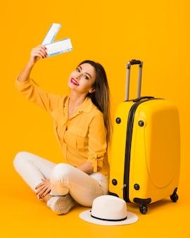 スマイリー女性が飛行機のチケットを保持しながら荷物の横にポーズ