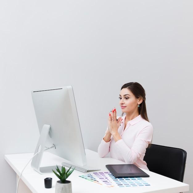 Вид сбоку женщины за столом, с тревогой глядя на компьютер