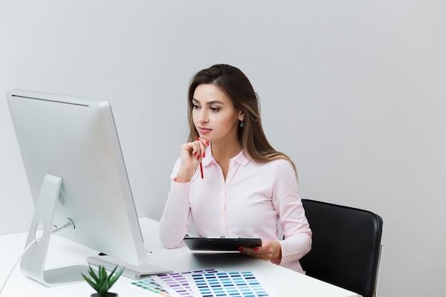 Вид спереди работающей женщины, глядя на компьютер и держа планшет