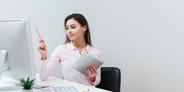 タブレットを押しながら机で働く女性