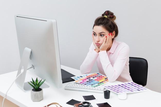 Побежденная женщина сидя на столе и смотря компьютер