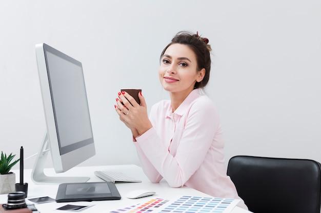 Женщина за столом, наслаждаясь чашечкой кофе