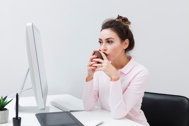 Женщина за столом пьет кофе и смотрит на компьютер
