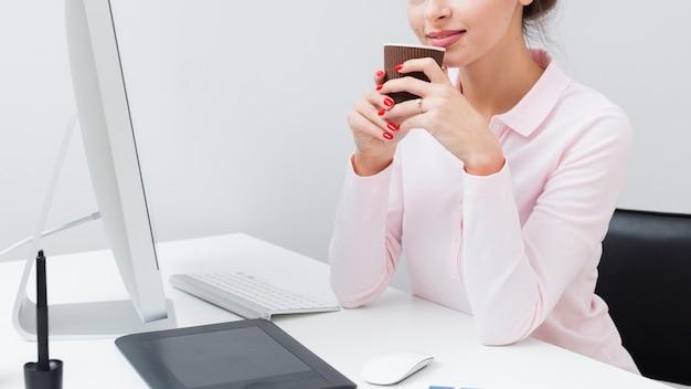 Вид сбоку работницы за столом, держа чашку кофе