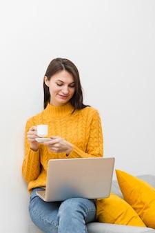 ソファに座って一杯のコーヒーを保持している膝の上のラップトップを持つ女性