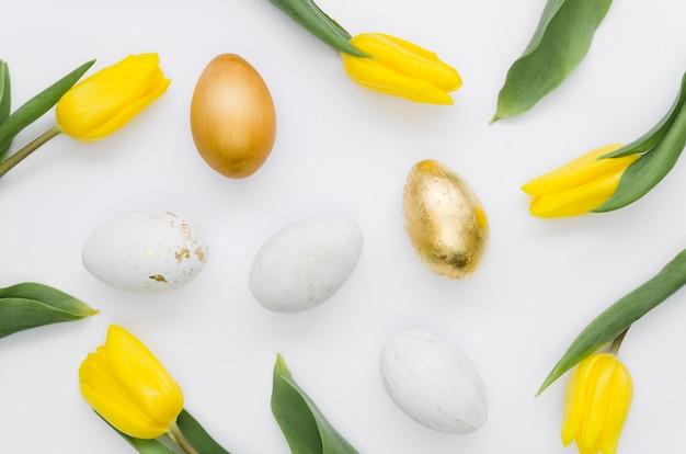 Плоская кладка золотых пасхальных яиц с тюльпанами