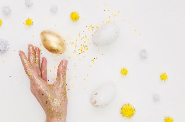 Плоская кладка золотого яйца на пасху с блеском и одуванчиками
