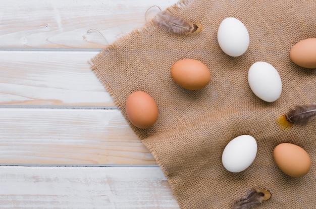 Вид сверху неокрашенные яйца на пасху с мешковиной и копией пространства