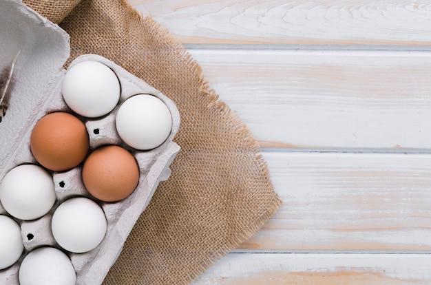 Вид сверху коробки яиц с мешковиной и копией пространства