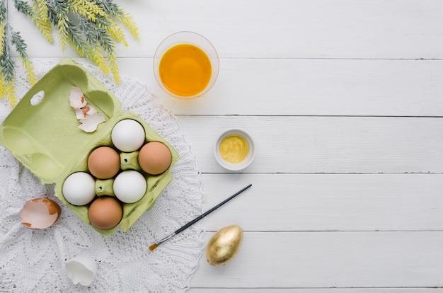 Вид сверху яйца в коробке на пасху и краситель с кистью
