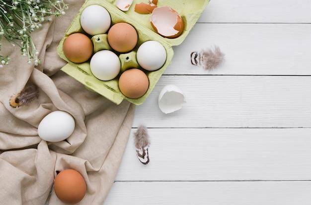 植物とコピースペースとイースターのカートンで卵のトップビュー