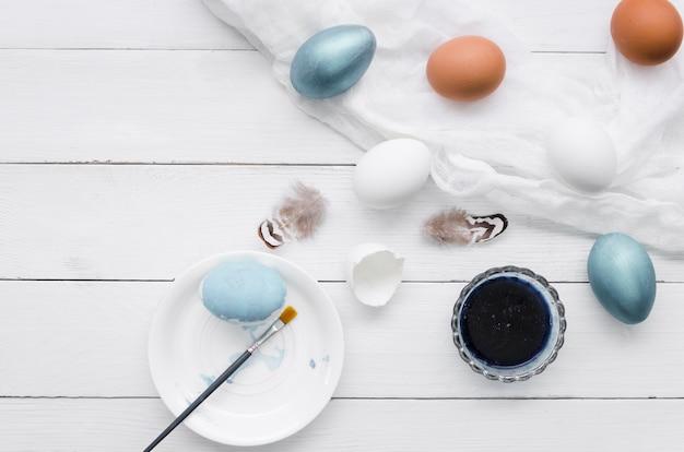 Вид сверху на пасхальные яйца с краской и перьями