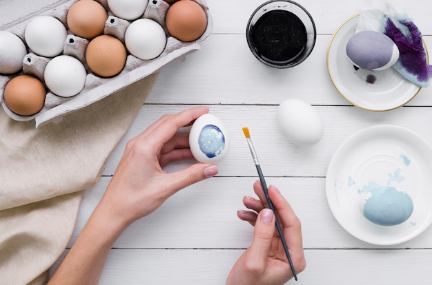 Взгляд сверху рук крася яичко на пасху с коробкой и краской
