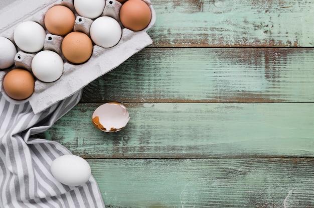 Вид сверху неокрашенные яйца в коробке на пасху