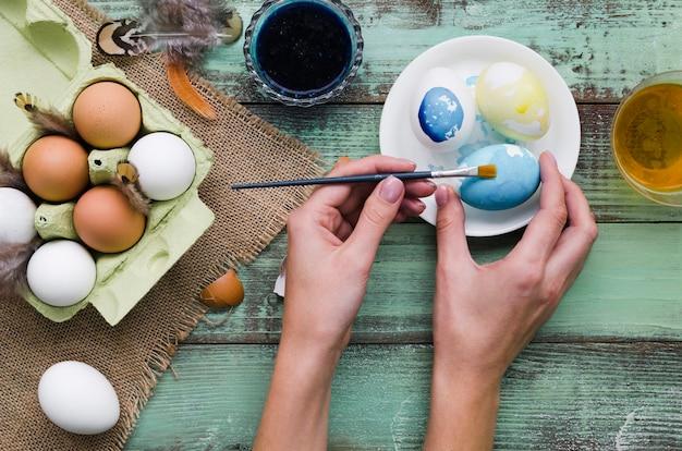 Вид сверху руки красящие яйца на пасху