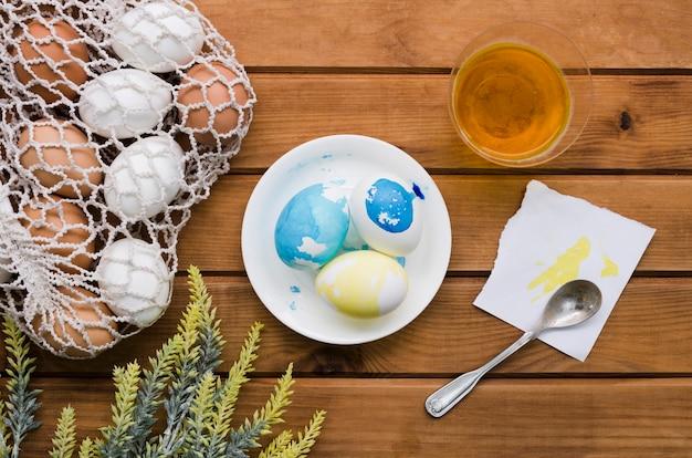 Вид сверху на пасху яйца в сетке с краской и растений